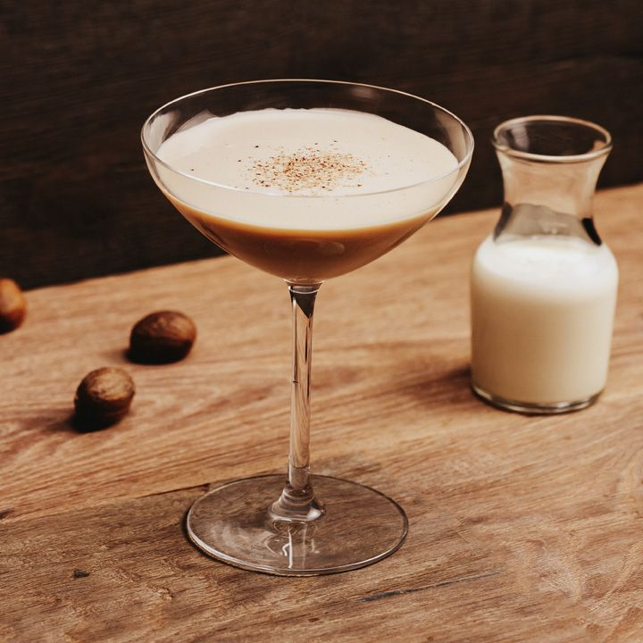 Brandy Alexander cocktail on a wooden table with whole nutmeg and carafe of cream
