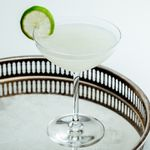 vodka gimlet cocktail with lime wheel garnish, served on a metal tray