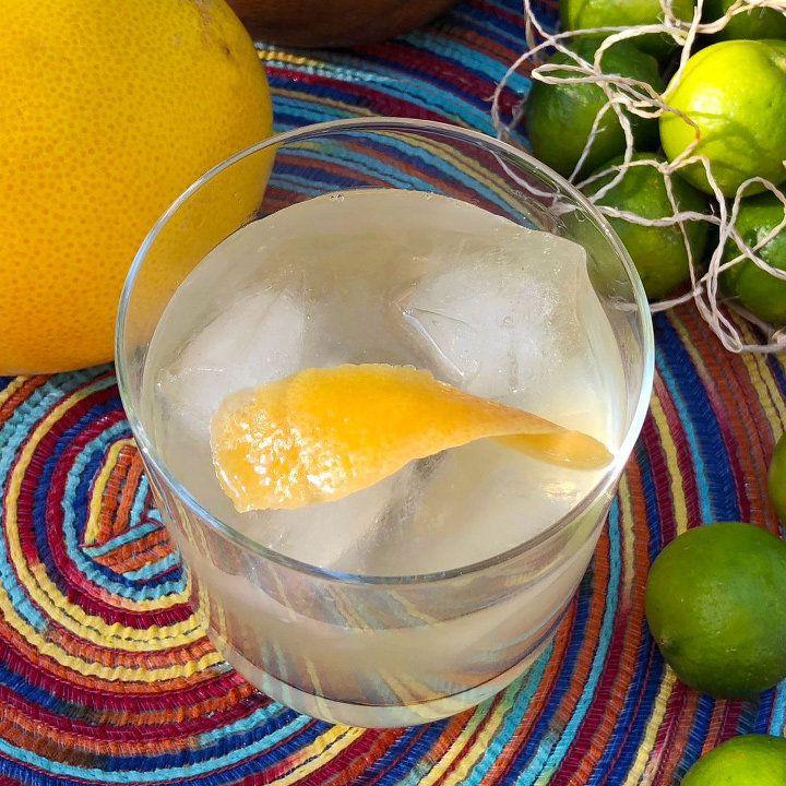 A birdseye view of a shaken cocktail in a rocks glass garnished with a manicured orange twist