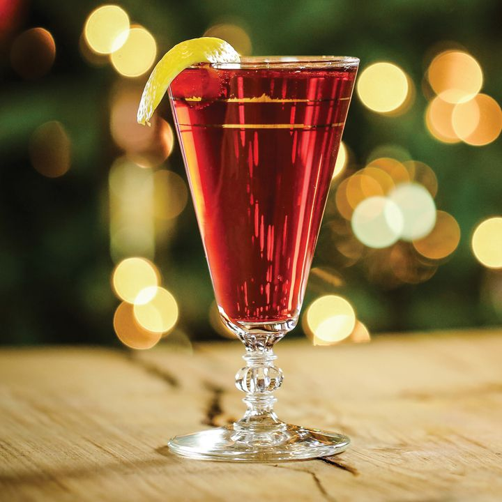A wide champagne flute with a knobbed stem rests on a wooden surface. The background is blurry golden lights against green, and the glass is filled with a bubbly red drink, garnished with a lemon peel.