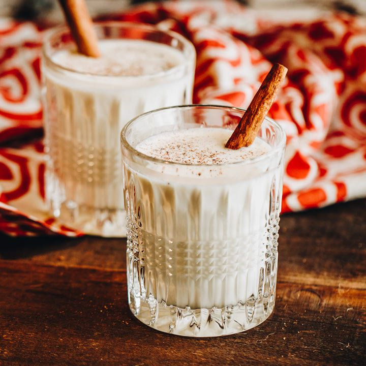 two eggnog cocktails with cinnamon sticks and nutmeg garnish