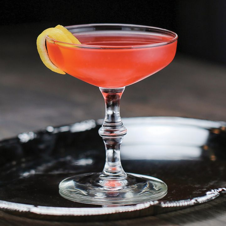 An elegant coupe glass holds a bright red drink with a thin slice of lemon peel. The glass sits on a silver tray