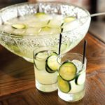 two tumblers of Green Beast punch with cucumbers, sitting in front of a full punch bowl with ice, cucumbers and ladle