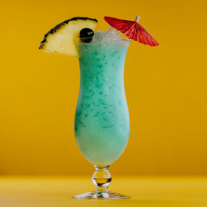 blue hawaiian cocktail with pineapple and umbrella garnish, set against a yellow background