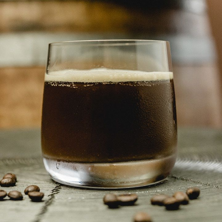 Eye Opener cocktail in a rocks glass with white froth, served next to coffee beans