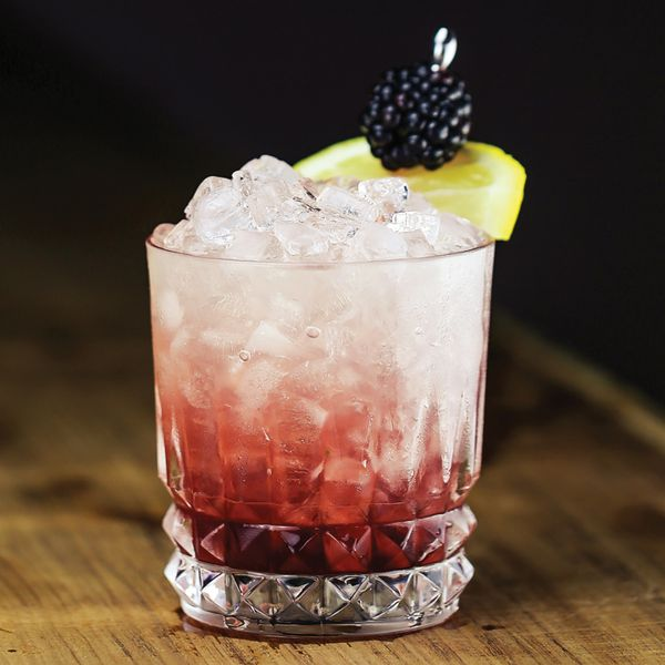 bramble cocktail over crushed ice with blackberry and lemon garnish