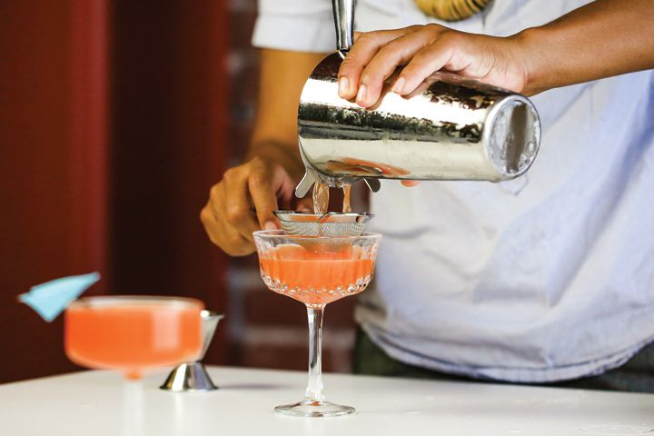 A bartender fine-straining a deep orange Paper Plane cocktail into a coupe glass