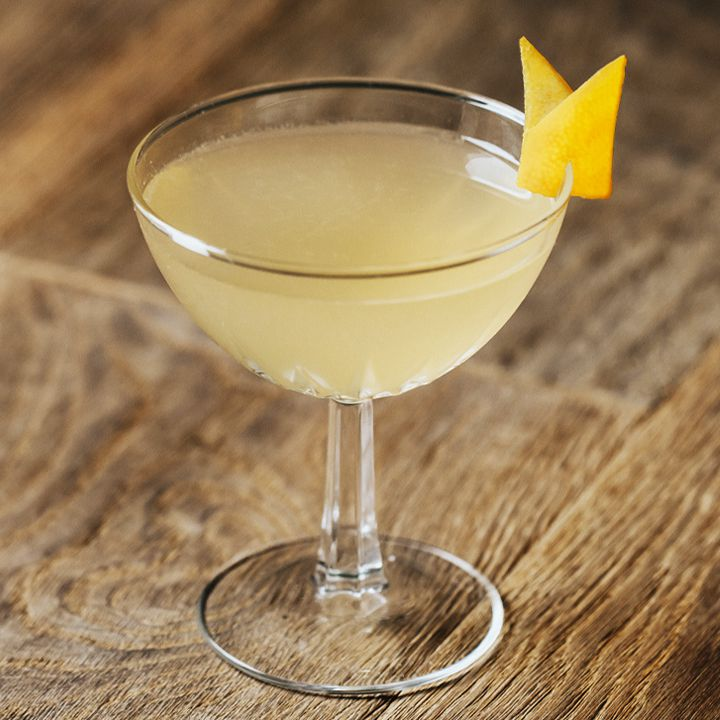 Bee's Knees cocktail in a coupe with lemon peel garnish