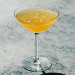 A narrow-stemmed cocktail glass with a wide brim holds a pale orange cocktail. A few bubbles on the surface reveal how recently it was poured, and the orange of the drink is set off against the gray marble backdrop.