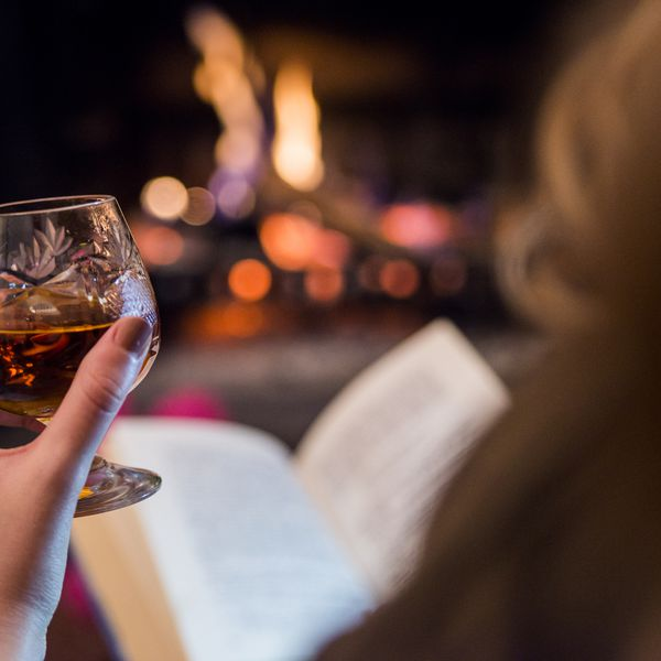 woman reading a book by a fireplace with a whiskey or brandy in a glass.