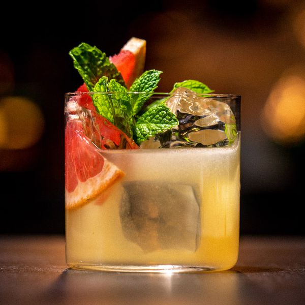Kyoto Sour cocktail with clear ice in a thin-walled rocks glass, garnished with grapefruit wedges and mint