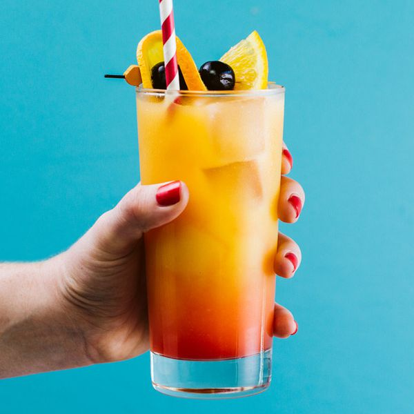 hand with red nail polish holding a tequila sunrise cocktail