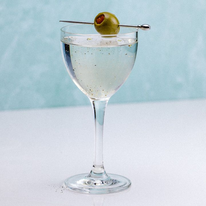 On a white counter with a sky-blue background, a beautiful curved Nick & Nora glass holds a Martini. The drink is slightly cloudy and decked with spots of pepper. A single pepper-stuffed olive is pierced on a silver skewer resting across the mouth of the glass.