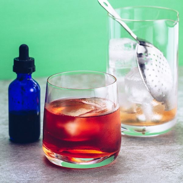 A deep red Negroni in a rocks glass between a blue dropper bottle and a mixing glass filled with ice