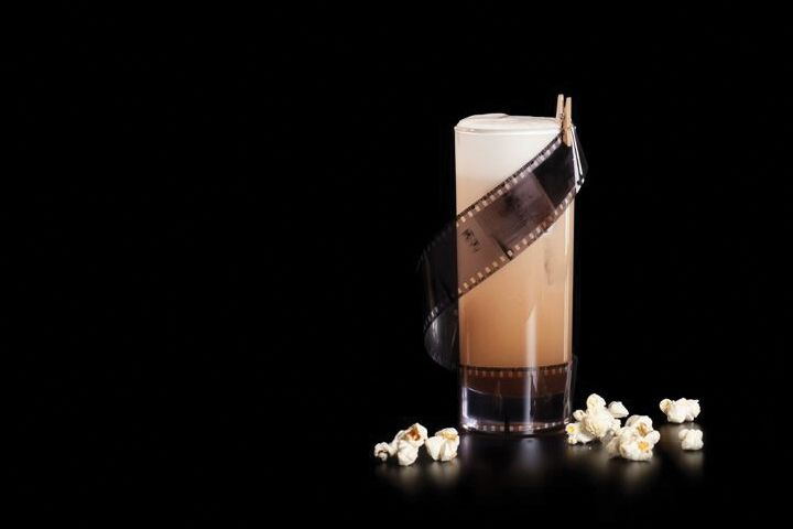 Trillby & Chadwick Detectives Agency cocktail with roll of film garnish and popcorn scattered around it