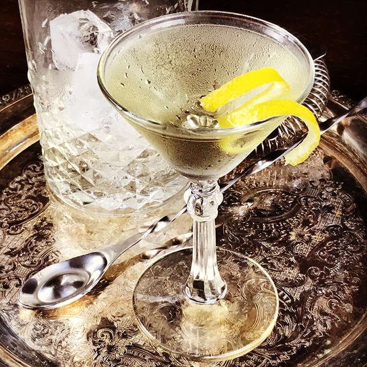 A Martini glass with a knobby stem sits on a silver bar tray with intricate inlay. It is garnished with a long twist of lemon peel. Also on the bar tray is a long bar spoon, a Hawthorne strainer, and a mixing glass with ice cubes.