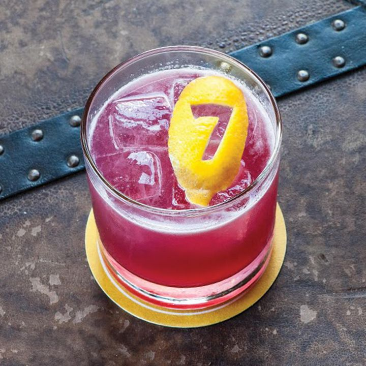 A bright purple shaken cocktail on ice in a clear rocks glass, garnished with a lemon coin with the number 7 carved into it and served atop a gold coaster set on a brown and black leather background