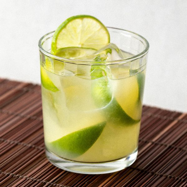 Caipirinha cocktail in a rocks glass with limes, served on a bamboo mat