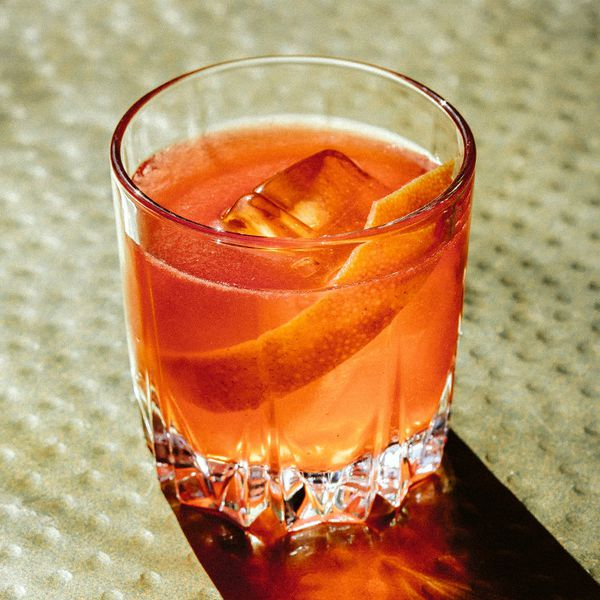 Grapefruit Negroni in a rocks glass, with one large ice cube and a large, wide grapefruit peel
