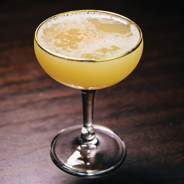 yellow-colored Smoke Show cocktail in a gold-rimmed coupe