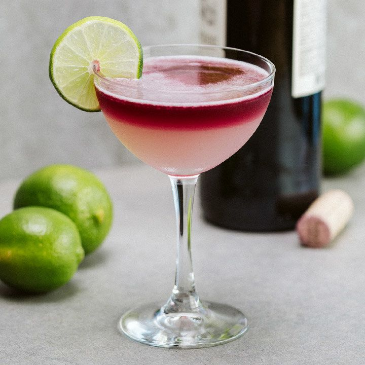 devil's margarita cocktail next to limes and red wine bottle