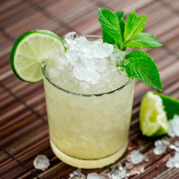 Crushed ice and pale spirits fill a short rocks glass, which rests on a wooden curtain. Ice and lime spill out of the cup, and the drink is garnished with mint and a lime wheel.