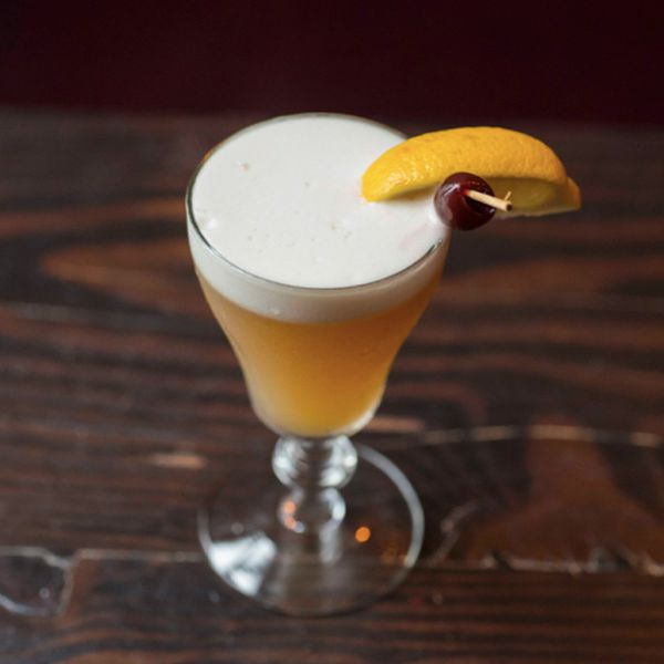 A sour glass rests on hardwood and holds a beautiful Whiskey Sour, complete with a thick layer of white foam, as well as a lemon wedge garnish and a cherry on a wooden skewer.