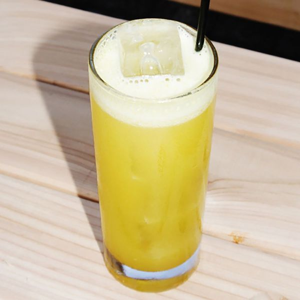 yellow-colored Delhi Cooler cocktail in a Collins glass, served over ice with a black straw