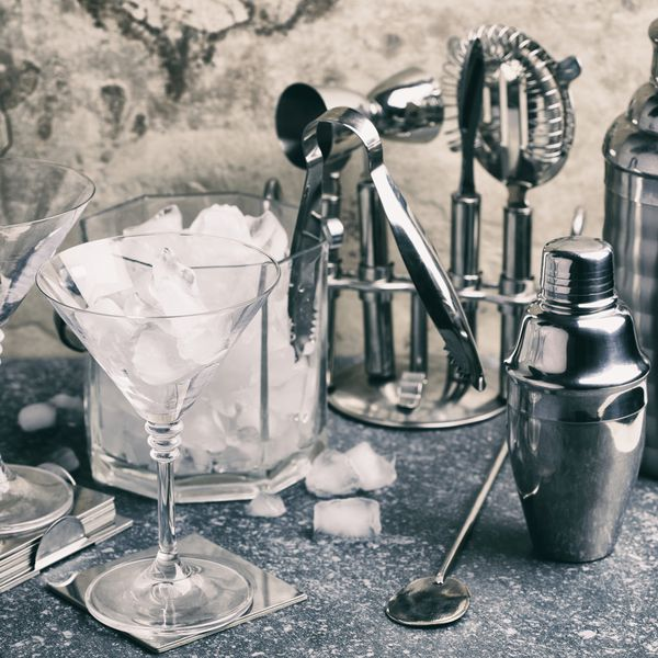 A set of bar tools for making a cocktails arranged on a stone background.