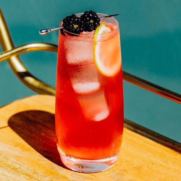 oaks lily cocktail garnished with two skewered blackberries, served on a bar cart