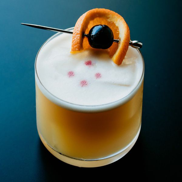 Shot from a dramatic upper angle, this cocktail in a rocks glass is a whiskey-brown, topped with a thin layer of egg whites that is dotted with four drops of red wine. A cherry and an orange wheel on a pick garnish the glass, and its background is a dark blue that fades to black.