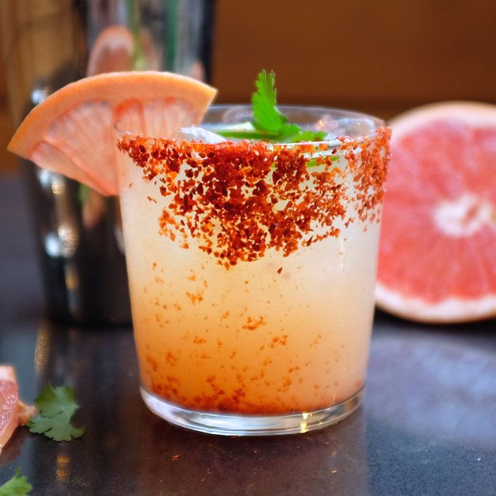 Vida Paloma cocktail in a chile piquin-rimmed rocks glass, garnished with a grapefruit wedge, jalapeño round and cilantro