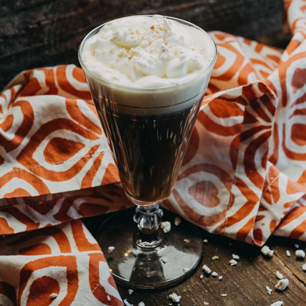 Gran Rosta Coffee cocktail in an Irish Coffee mug with whipped cream topping, served next to orange-and-white towel