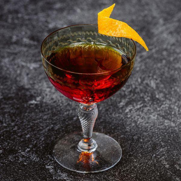 An elaborate cocktail glass with a detailed stem holds a vivid red Old Fashioned. The fancy glass is garnished with a twist of orange zest and sits on a black and gray surface