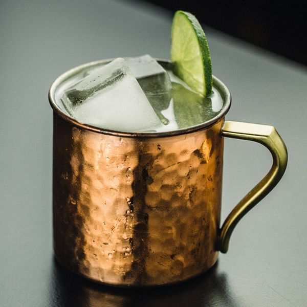 moscow mule cocktail served in a copper mug with a lime wheel