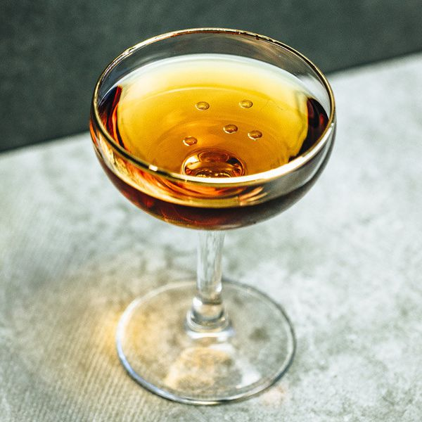 A cocktail coupe on a gray surface holds a copper-toned rum and sherry cocktail. Five droplets of olive oil glisten on the surface of the drink.