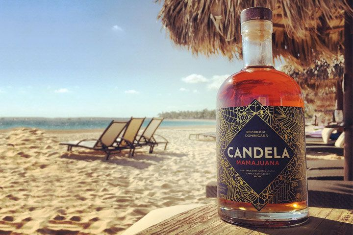 A bottle of reddish-brown Candela Mamajuana pictured on a beach beneath a straw umbrella