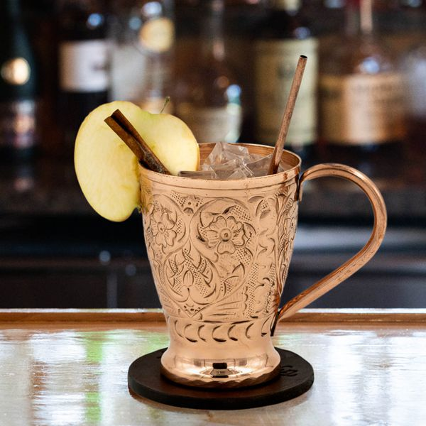 A tapered copper Moscow Mule mug has intricate flower designs on it and a swooping handle. It rests on a leather coaster on a reflective bar top, with ice poking up, a slice of apple and cinnamon stick as garnish.