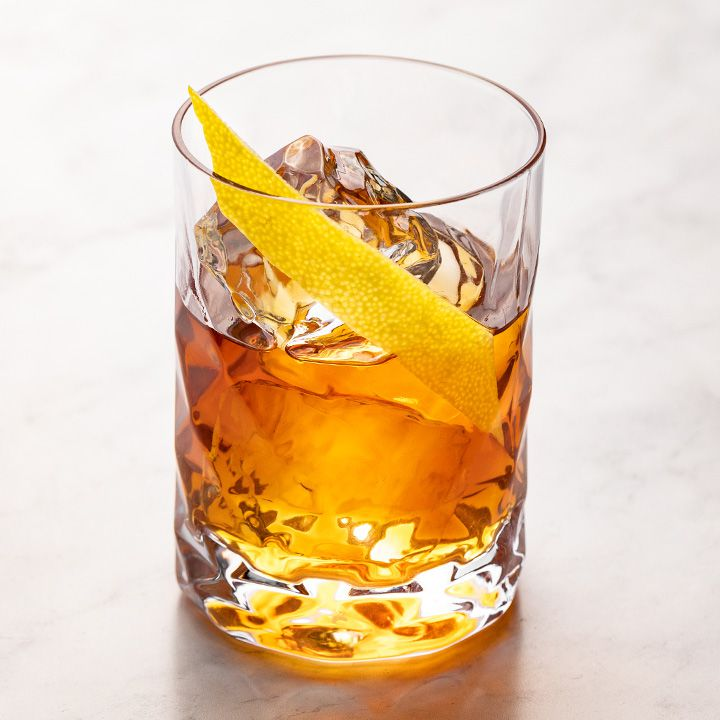 A tall, narrow rocks glass holds some ice cubes and an orange-hued drink. A long, angular piece of lemon peel garnishes the drink, and the whole thing is set against white marble.