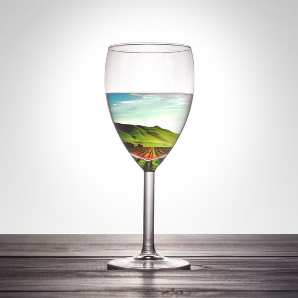 A glass of wine filled with a view of a sunny vineyard