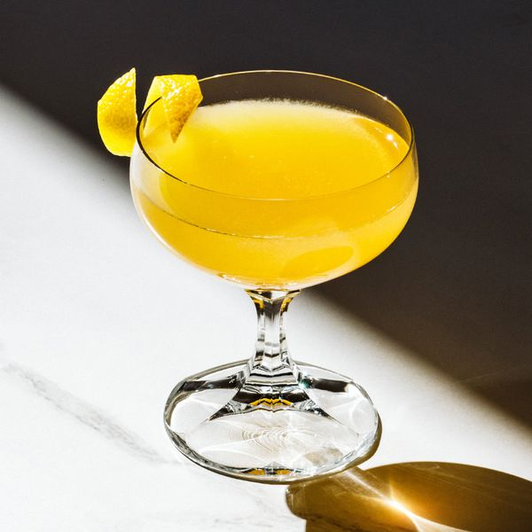 A bright yellow shaken cocktail served in a short coupe glass with a dramatic beveled stem; the drink is placed on a white marble surface with a dark, shadowy background