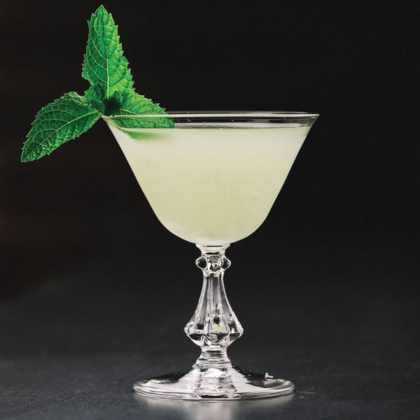South Side cocktail in a cocktail glass with ornate stem, garnished with mint sprig and set against a dark background