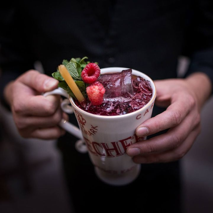 A cocktail at AnonymouS Bar. A dark maroon liquid fills a white mug and it is garnished with raspberries and a mint sprig