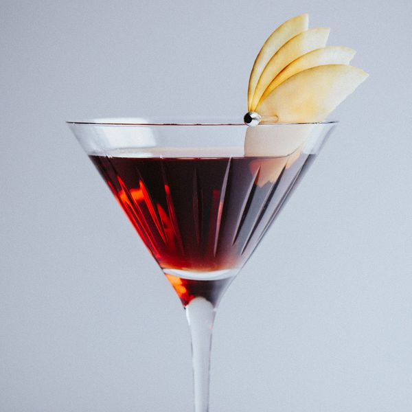 Dark-colored Kiss cocktail with glints of red, served in a cocktail glass and garnished with an apple fan of four apple slices on a skewer