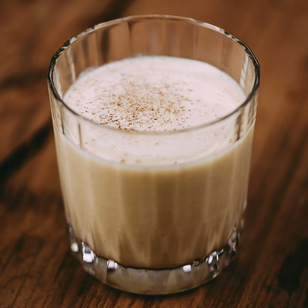 white and creamy Harvest Nog cocktail in a textured double rocks glass, with grated nutmeg on top