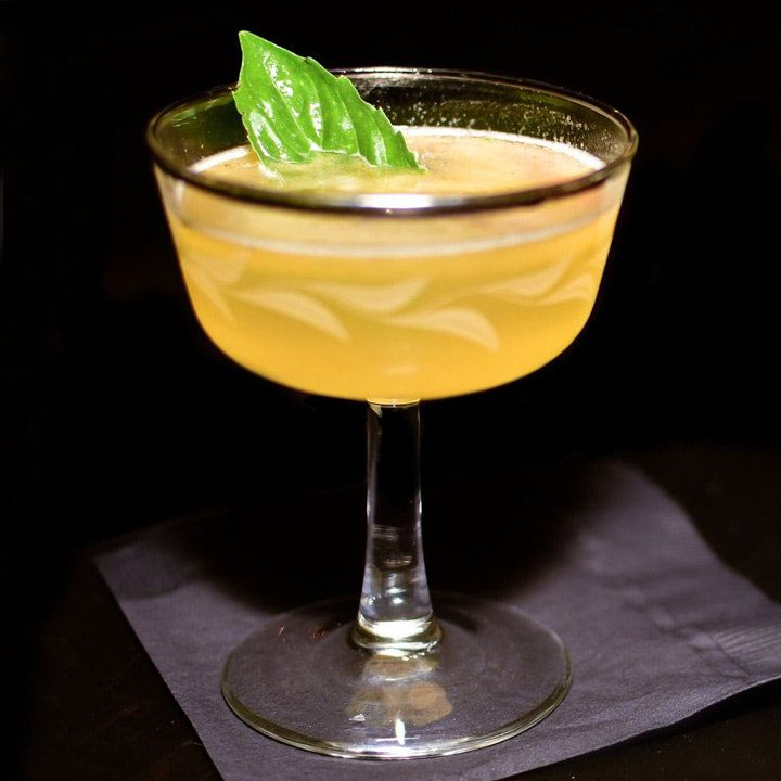 yellow-hued monastery cocktail in a gold-rimmed coupe, garnished with a basil leaf and served on a black napkin