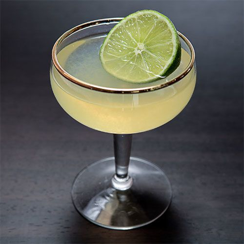 A gold-rimmed coupe glass holds a Daiquiri. It is garnished with a full lime wheel, and sits on a neutral, dark gray background.