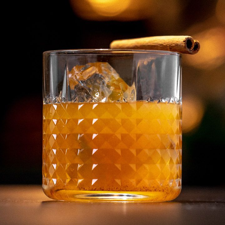 Pumpkin Spice Old Fashioned in a textured rocks glass with one large ice cube and a cinnamon stick balanced on the rim