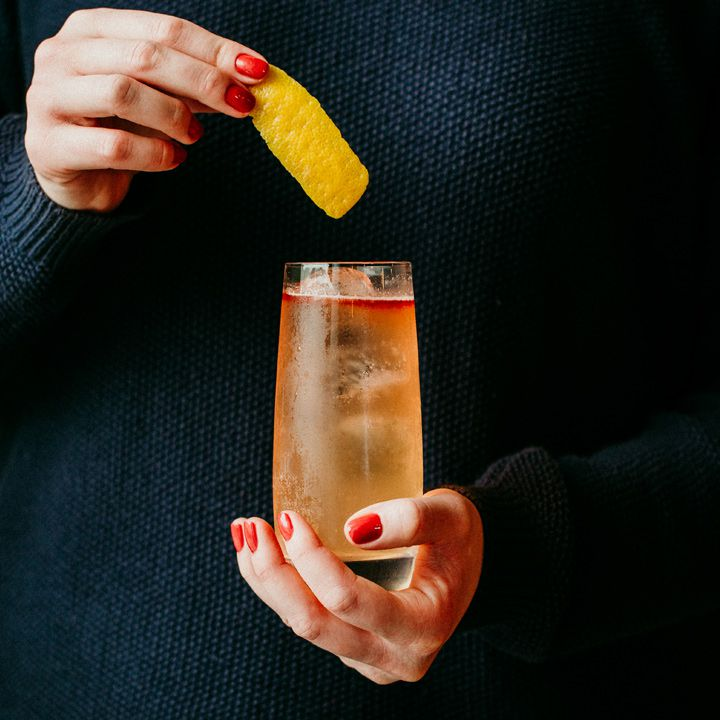 Hand placing a lemon peel into the Tequila Honey Bee cocktail