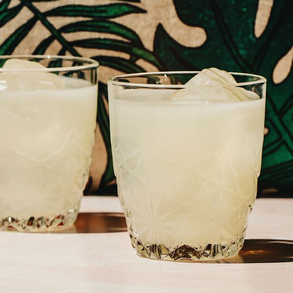 two rocks glasses of Garrick Club Punch over ice, served on a white surface in front of green foliage-print wallpaper